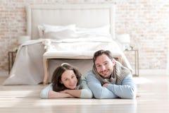 Couples positifs heureux se trouvant devant le lit Photos libres de droits