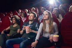 Couples positifs observant le film drôle au cinéma et mangeant du maïs éclaté Image stock