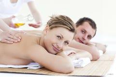 Couples positifs recevant un massage arrière avec le pétrole Photographie stock