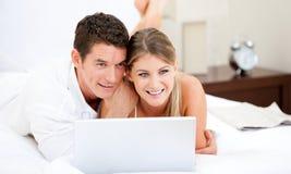 Couples positifs surfant sur l'Internet Images stock