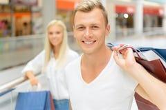 Couples positifs tenant des paquets Image stock