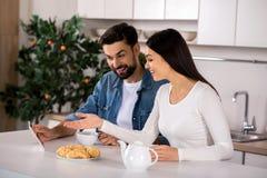 Couples positifs utilisant le comprimé dans la cuisine images libres de droits
