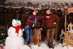 Couples près du bonhomme de neige d'intérieur regardant le bon cadre Image libre de droits