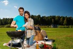 Couples préparant des saucisses dehors Image stock