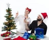 Couples préparant l'arbre de Noël Photographie stock libre de droits