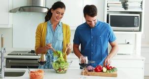 Couples préparant la nourriture ensemble dans la cuisine banque de vidéos