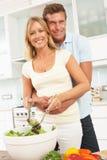 Couples préparant la salade dans la cuisine moderne Photos stock