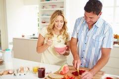 Couples préparant le petit déjeuner sain dans la cuisine Image stock