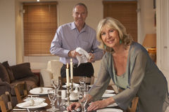 Couples préparant le Tableau pour un dîner Photo stock