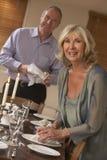 Couples préparant le Tableau pour un dîner Image stock