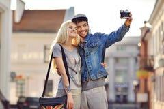 Couples prenant des photos d'autoportrait avec le vieil appareil-photo Photos libres de droits