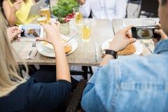 Couples prenant des photos de leur nourriture Photographie stock