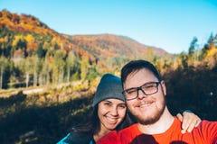 Couples prenant l'autoportrait en montagnes avec le smartphone Photos stock