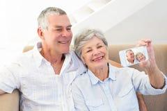 Couples prenant l'autoportrait par le téléphone intelligent Photographie stock libre de droits