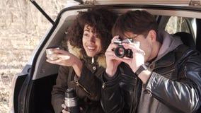Couples prenant la photo utilisant l'appareil photo numérique se reposant dans le tronc de voiture banque de vidéos