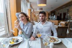 Couples prenant le déjeuner au restaurant gastronomique rustique Image libre de droits