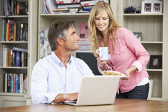 Couples prenant le déjeuner fonctionnement dans le siège social ensemble photographie stock libre de droits