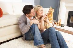 Couples prenant le jeu avec le chat d'animal familier à la maison Image stock