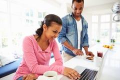 Couples prenant le petit déjeuner et à l'aide de l'ordinateur portable dans la cuisine photo stock
