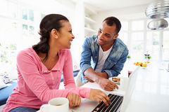 Couples prenant le petit déjeuner et à l'aide de l'ordinateur portable dans la cuisine images stock