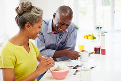 Couples prenant le petit déjeuner et lisant le magazine dans la cuisine image stock