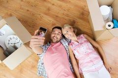 Couples prenant le selfie avec le smartphone sur le plancher Photos stock
