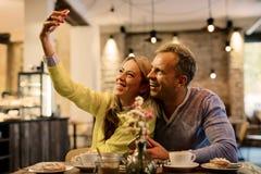 Couples prenant le selfie en café Photo libre de droits