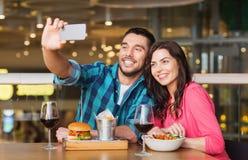 Couples prenant le selfie par le smartphone au restaurant Photographie stock