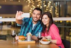 Couples prenant le selfie par le smartphone au restaurant Photos libres de droits