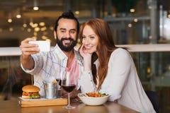 Couples prenant le selfie par le smartphone au restaurant Images stock