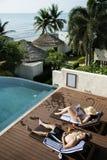 Couples prenant un bain de soleil par la piscine Photo stock