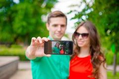 Couples prenant un selfie par le smartphone Jeune homme faisant l'amie de photowith sur la rue riant et ayant l'amusement dedans Photo libre de droits