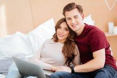 Couples réfléchis embrassant étroitement et souriant Images stock