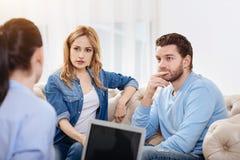 Couples réfléchis gentils écoutant le psychologue Images stock