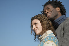 Couples réfléchis regardant loin contre le ciel bleu clair Image libre de droits