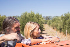 Couples réfléchis tenant le tracteur proche dans la ferme olive Photo libre de droits