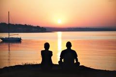 Couples rétro-éclairés admirant le lever de soleil au-dessus de la mer Photographie stock libre de droits