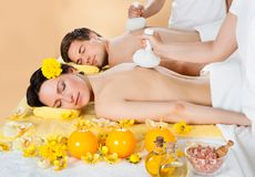 Couples recevant le massage avec les timbres de fines herbes de compresse à la station thermale Photographie stock
