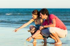Couples recherchant des coquilles au coucher du soleil Image libre de droits