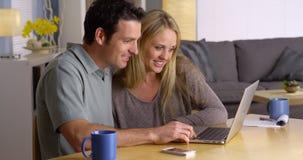 Couples recherchant des fuites de vacances sur l'ordinateur portable Photos stock