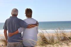 Couples regardant à l'extérieur à la mer Image stock