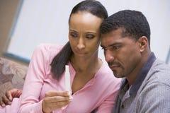 Couples regardant à la maison l'essai de grossesse Photos libres de droits