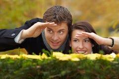 Couples regardant au-dessus d'une haie Image stock