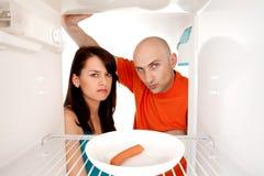 Couples regardant dans le réfrigérateur Photo libre de droits