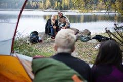 Couples regardant des amis se reposant dans la tente Image stock