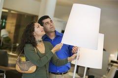 Couples regardant des lampes dans le magasin de meubles photographie stock libre de droits