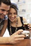 Couples regardant des photographies sur l'appareil photo numérique le café de trottoir Photo stock