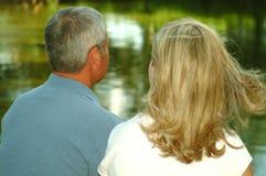 Couples regardant l'étang photos stock