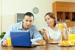 Couples regardant l'email   pendant le petit déjeuner Photo libre de droits