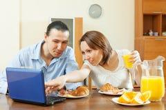 Couples regardant l'email  pendant le petit déjeuner Photos stock